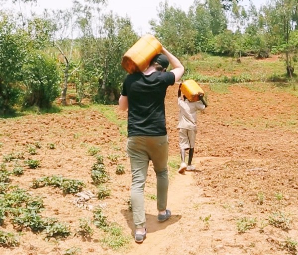 Our co-founder Daniel learning about Vianney's water walk when we visited our water project in Burundi